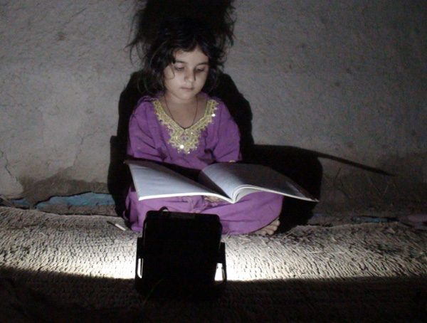Girl reading by LEDtronics donated LED light.  GCitizenship.com
